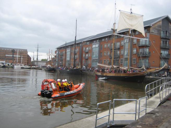View of Gloucester Docks with a series of tall ships, and an orange search and rescue vessel in foreground.