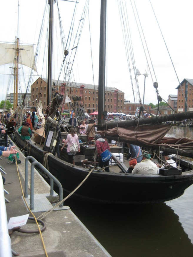 View of visitors aboard a sailing ship in harbour to give a sense of the small scale of the vessel.