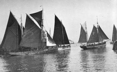 Black and white photographs of several Lowestoft smacks under full sail.