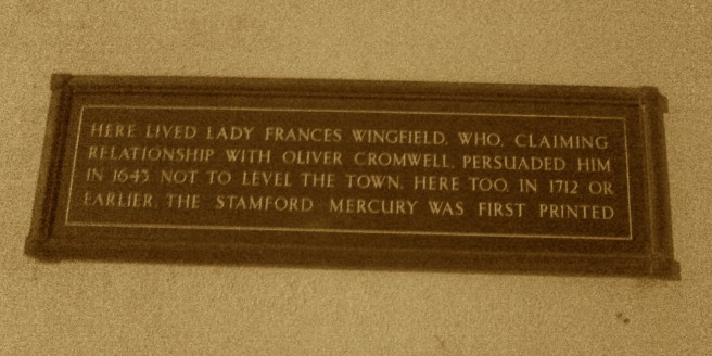 Sepia photograph of dark plaque, with text commemorating Lady Francis Wingfield and the founding of the Stamford Mercury, associated with the same building.
