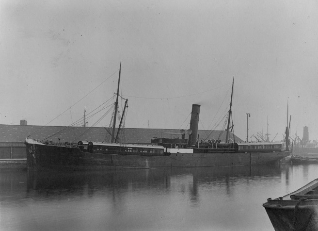 Black and white photo of steamship with single funnel, and four carriages aboard, partly reflected in the water below.