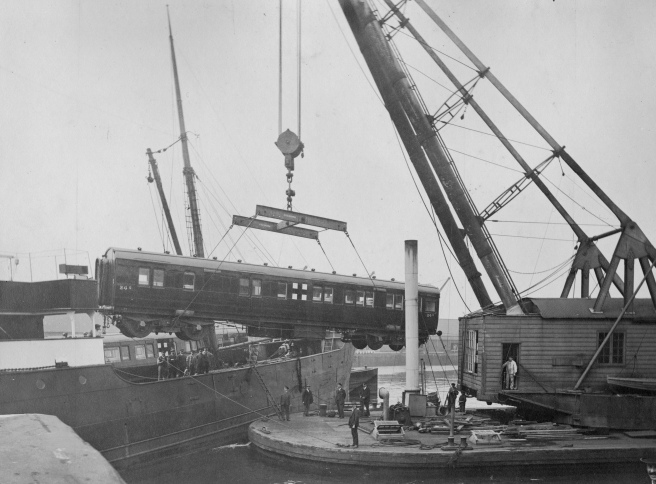 Black and white photograph of crane at right with suspended railway carriage over the deck of a ship.