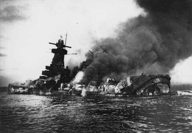 Black and white photograph of German warship on fire and sinking, with smoke billowing out of the vessel to the right.