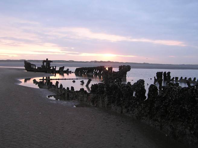 View of shipwreck on sands at sunset, showing skeleton of vessel.