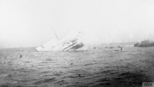 Black and white photograph of vessel sinking, throwing up spray, and resulting in visible sea turbulence.