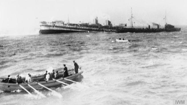 Black and white photograph of rowing boats in foreground and middle ground, steering away from sinking hospital ship in the background. To the right background a black vessel stands by to assist.