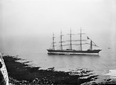 Black and white photograph of five-masted sailing ship aground in shallow water off a rocky coastline in the foreground.