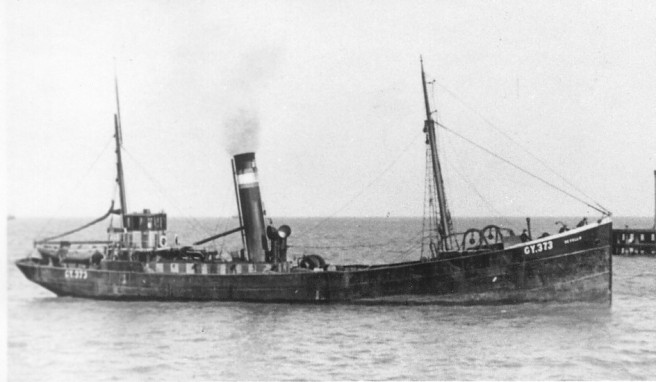 Black and white photo of steam trawler, with steam coming out of its funnel.
