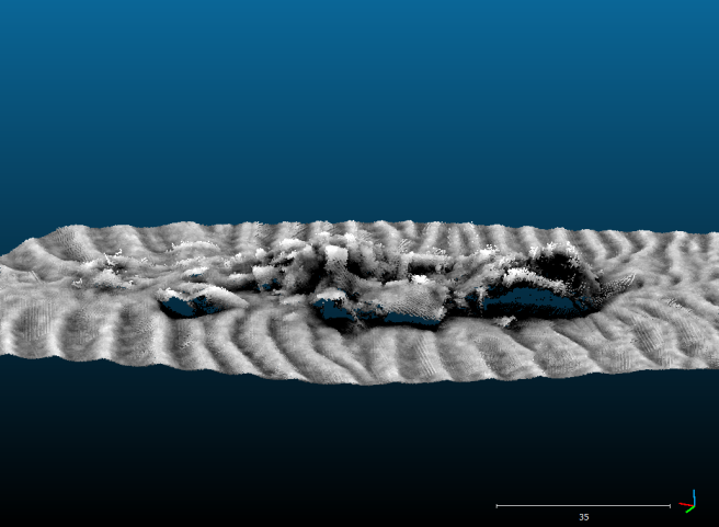 Computer-generated image of the wreck site on the seabed, showing a jumbled mass of darker metal in grey against a grey background of sandwaves.