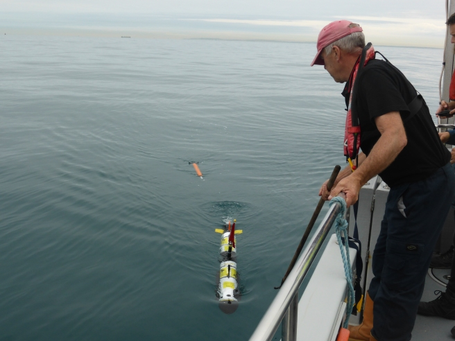 Man dressed in black to the right of the image looks over the railing of a boat at an underwater vehicle on the surface of the water to his left.