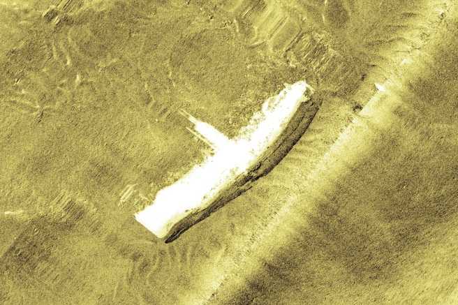 Side-scan sonar image showing vessel on its side, with its central structure clearly visible, picked out in white against an undulating textured yellowish brown background representing the seabed.