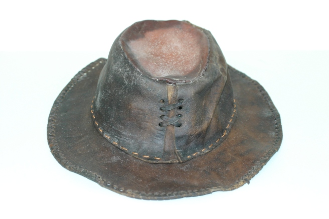 View of brown leather hat against a white background, showing that the crown of the hat is laced together with a decorative thong.
