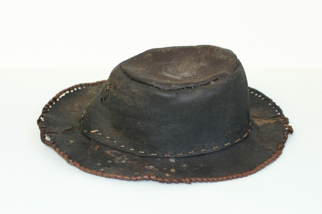 Side view of crown and brim of brown leather hat, against a wide background.