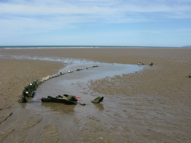 Stretch of sandy beach with a strip of water in the middle of the photograph, surrounding the timbers of a wreck protruding from the sand, set against a wide blue sky.