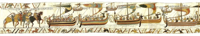 Multicoloured tapestry scenes of ships laden with men and horses, with horsemen waiting at the left side of the scene, embroidered on a cream background, with border decoration in the lower register, and at top left.