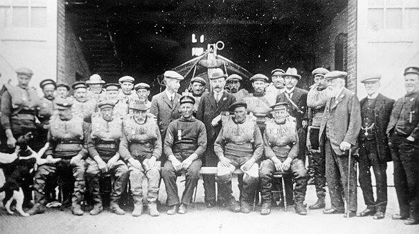 Black and white photograph of two rows of en, seated in front, standing at the back, in front of the open doorway through which the bows of a lifeboat can be seen.