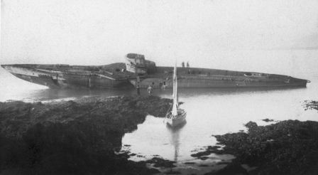 Black and white photo of a wrecked submarine, which bisects the photograph longitudinally. In the foreground dark rocks and an inlet, in which the white sail of a dinghy can be seen. The background grey, featureless sea and sky.