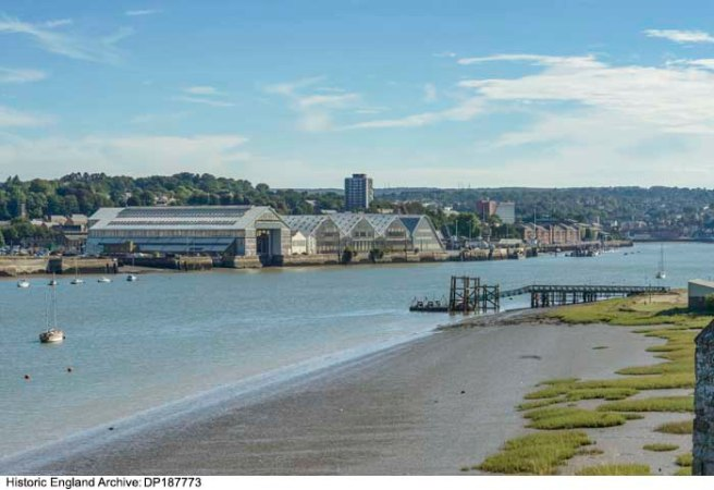 Colour photograph of blue river running diagonally through image from bottom left corner, on the right bank brown mud and a jetty structure, on the left bank the pitched roofs of the dockyard and other buildings.