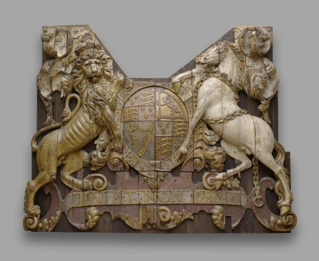 Carved wooden relief panel with some faded colour, showing 17th century royal shield of arms in centre, with lion supporter on left and unicorn supporter on right.