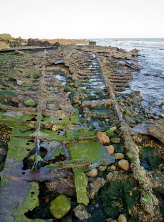 Portrait format photograph showing all that remains of the burnt-out Falcon, with the bottom ribs infilled with stones and green seaweed, sea lapping at the upper right-hand edge of the photograph.