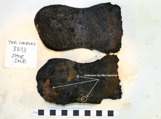 Two shoe soles one below the other, against a white background, and a centimetre scale rule underneath. Annotated on the lower sole where unknown tar-like materials have been seen.
