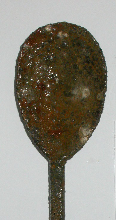 Bowl of a spoon, darkened with age and contact with water, against a plain grey background.
