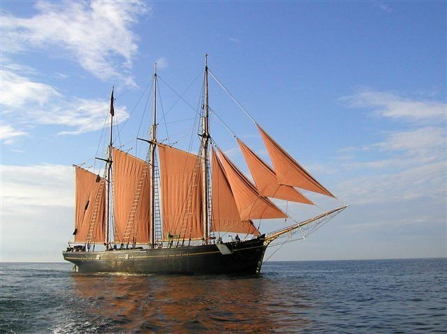 A ship in the centre of the image sits against a blue sky, the sea occupying the bottom third of the image. The ship has three masts, with three square red sails spread, and four triangular sails between the foremast and bowsprit, which faces to the right of the image.