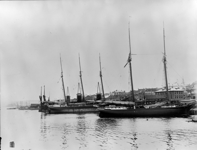 Black and white photograph of two ships in harbour, with water and reflections on the ripples in the foreground, and the black shapes of two ships and their masts without sails in the centre of the image: the one in the foreground is two-masted, with a three-masted ship in the background. The masts are silhouetted against the sky.