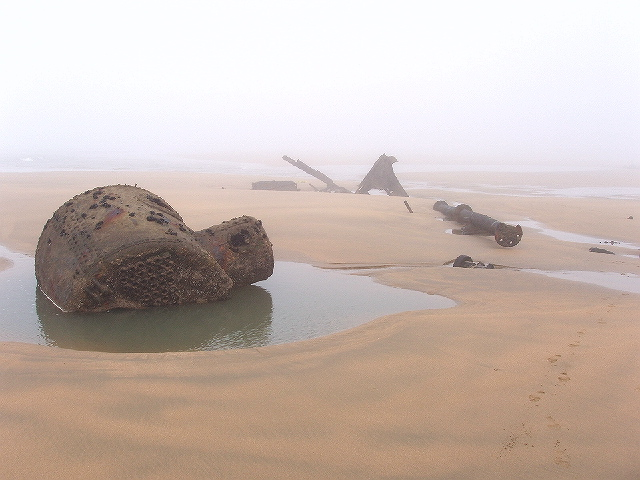 Three groups of dark metal elements of a wreck sitting in pools of water on a sandy beach, against a backdrop of grey mist.