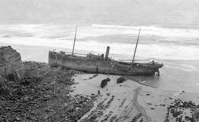 Black and white photograph of stranded ship, seen in profile broadside on to the beach, with rocks and stones visible in the lower half of the image. The ship is dry with the tide at the top of the image just lapping at the bottom of the vessel.