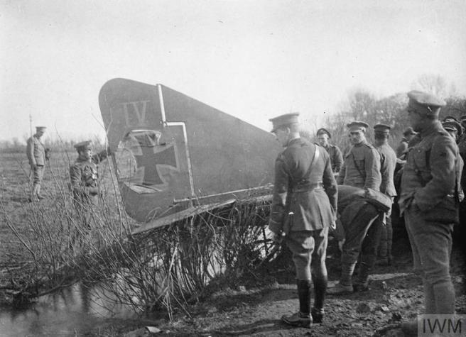 Black and white photograph of soliders standing around a crashed aircraft with a prominent black cross on its tailfin.