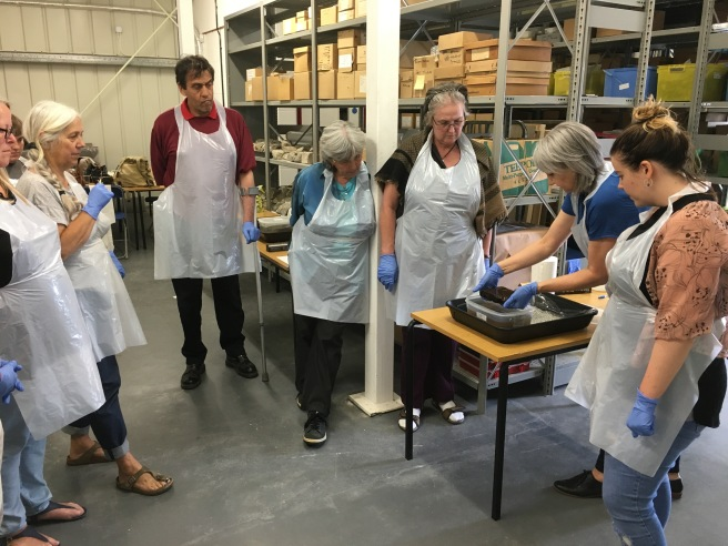Group of people standing in a semi-circle and all wearing blue conservation gloves,watching conservators working with object on table at right. Background is shelves of museum storage boxes.