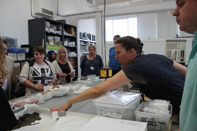 Participants standing around table in museum store listening to conservator speaking at right, with her arm stretched out across the table, which is covered with boxes and objects sitting on white conservation tissue.
