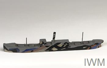 3D ship model painted in colour with abstract black patterns, photographed against a grey background.