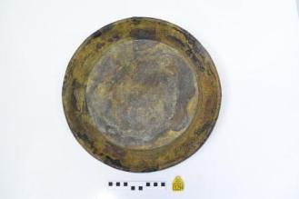 Pan after cleaning, with concretion removed, showing a darker metal colour and some discolouration. Scale rule and yellow tag below.
