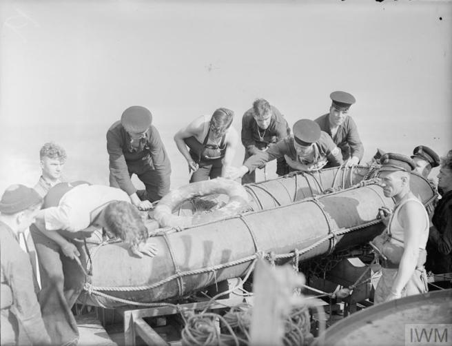 B&W photograph of men in uniform around an inflatable liferaft.