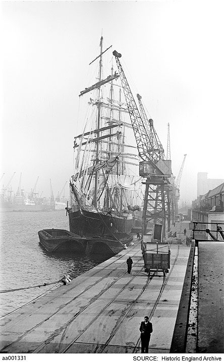 B&W photo of a dockside receding to show dockside cranes. To left a tall ship whose masts reach above the dock cranes.