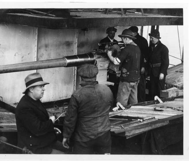 Contemporary black and white photograph of merchant seamen, two men in foreground, with gun in background being manned by crew to right.