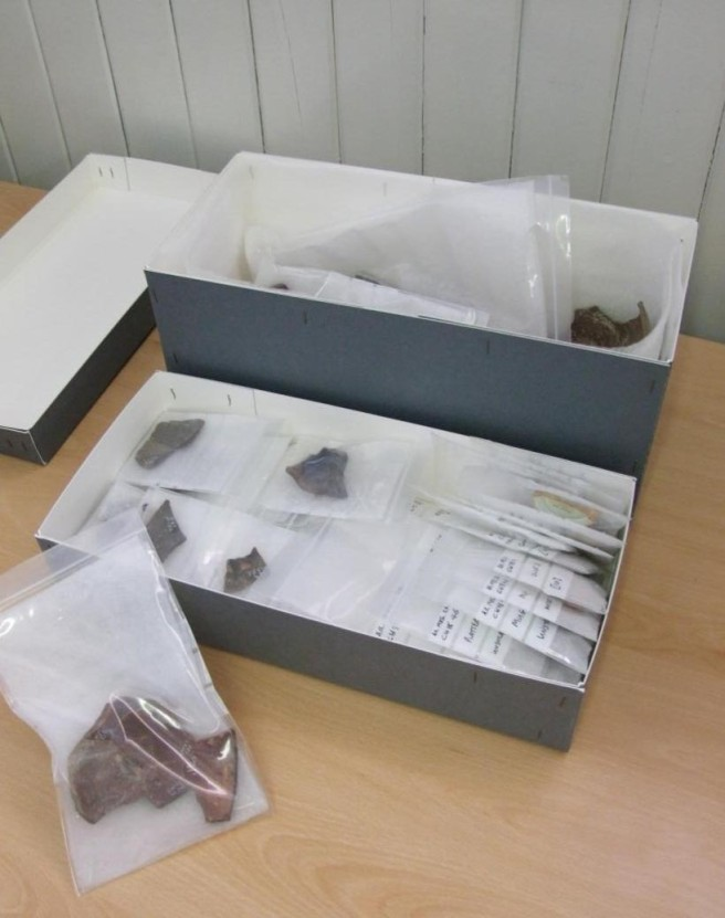 Open archive boxes displaying stored archaeological artefacts.