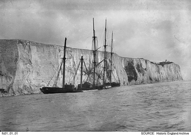 Historic B&W photo of shipwreck against cliffs, seen from seaward, sea filling the lower third of the image.