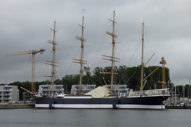 Modern colour photograph of four-masted museum ship with four bare masts and a crane beyond at left, against a grey sky.
