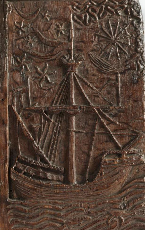 Wood carving of a medieval ship seen broadside on, on a wavy sea, with a tall mast and sunrays to top right.