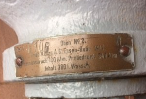 Detail of metal plate on neck of white air cylinder, engraved in German.