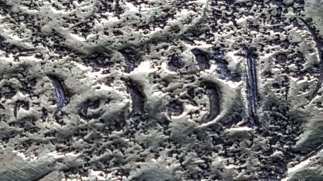 Detail view of corroded and pitted metal in which the numbers 5 3 3 1 are just legible.