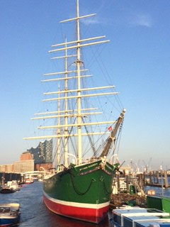 Bow and masts of a tall ship painted green, with a white band and red keel, in harbour, against a blue sky.