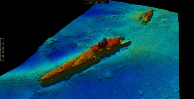 Multibeam image of wreck on seabed, with blues representing depths, greens areas of sandbank, and reds the upstanding wreck structure, broken in two, orientated lower left to upper right of image.