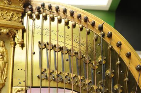 Detail view of top of harp, showing strings and pegs with engraved lettering on a metal plate underneath.