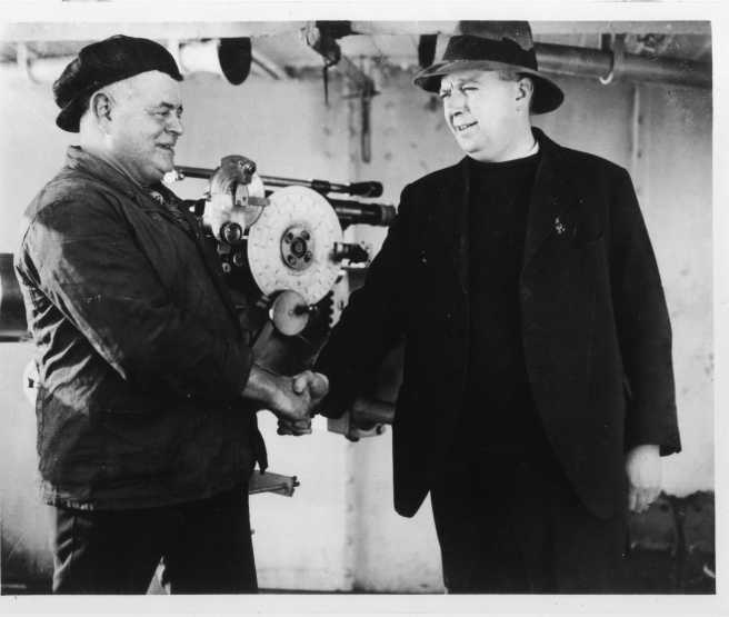 Historic black and white photograph of two men in shabby merchant seamen's clothes, shaking hands in front of a gun.