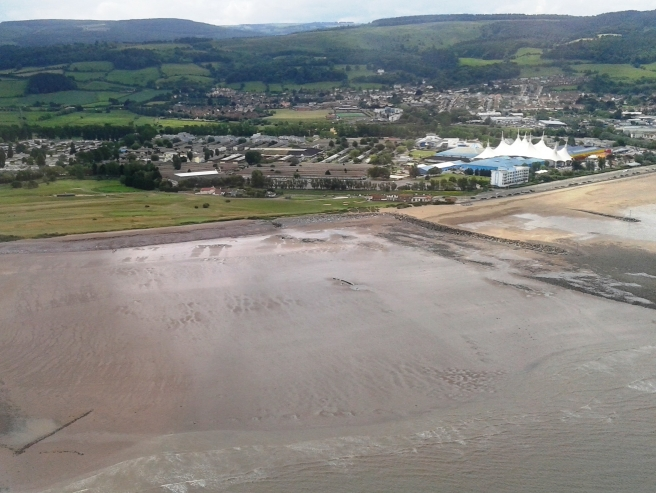 Aerial view of beach with small wreck visible at centre right, with green fields and hills beyond.