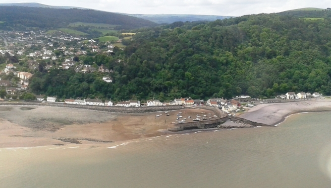 View of sea to bottom of image, beach at centre left to middle, with town and green wooded area to background of image.
